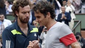 Roger Federer stringe la mano ad Ernests Gulbis che lo ha appena battuto