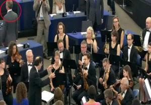 Nel cerchio un eurodeputato di Ukip che volta le spalle all'orchestra