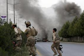 Members of Afghan security forces cross a road as smoke billows from the site of an attack near the Afghan parliament in Kabul, Afghanistan