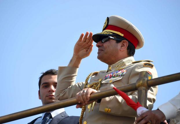 Egyptian President Abdel Fattah al-Sisi stands in boat on the Suez Canal as he attends the celebration of an extension of the Suez Canal in Ismailia