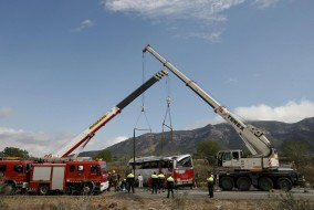 The wreckage of a bus is lifted by cranes after a traffic accident in Freginals, Spain, March 20, 2016.  REUTERS/Albert Gea