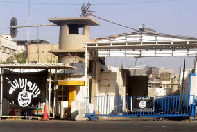 epa04330805 A black flag used by the the jihadist Islamic State of Iraq and Syria (ISIS), which now goes by the name the Islamic State (IS) hangs at the entrance of Nineveh governorate in Mosul city, northern Iraq, 25 July 2014. The United Nations' claims on 24 July 2014, that the Islamic State militia is ordering women in northern Iraq to undergo genital mutilation are in the process of being verified. The news comes after Jacqueline Badcock, the UN humanitarian chief in Iraq, told reporters that a fatwa, or religious edict, had reportedly been issued ordering women to undergo the brutal procedure.  EPA/MOHAMMED AL-MOSULI